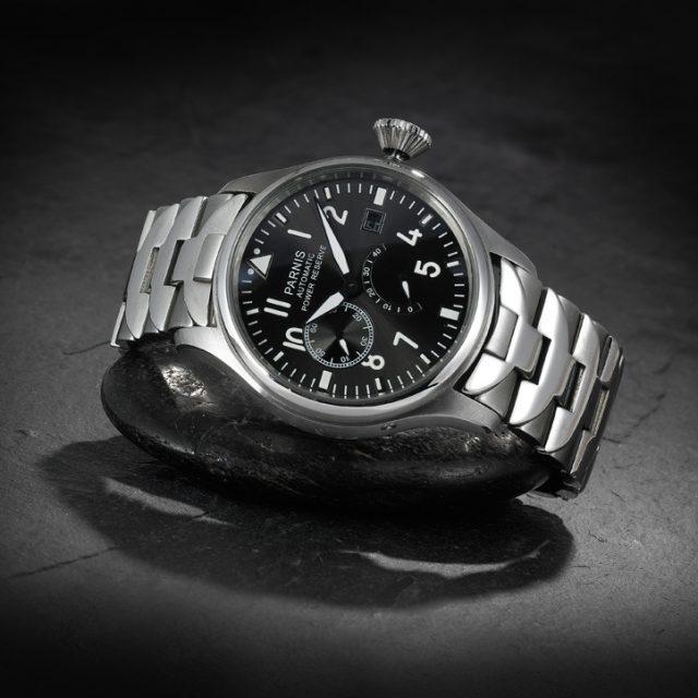 Parnis Armbanduhr aus Metall im Ambiente auf schwarzer Schieferplatte und Naturstein