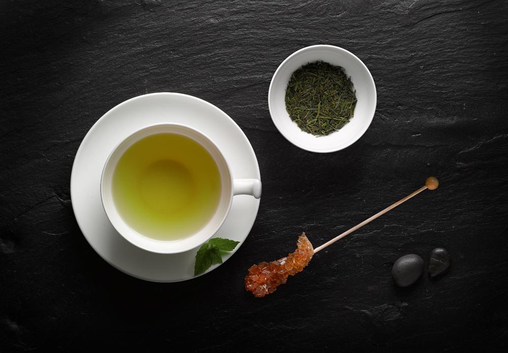 Tasse grüner Tee mit Kandis auf schwarzer Schieferplatte mit Natursteinen und Minze im Ambiente
