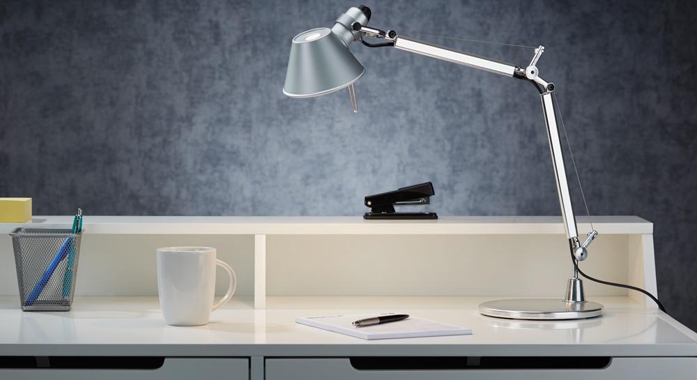 Artemide Tolomeo Mini aus Aluminium im Ambiente auf einem Schreibtisch mit Tacker Tasse und Büroutensilien